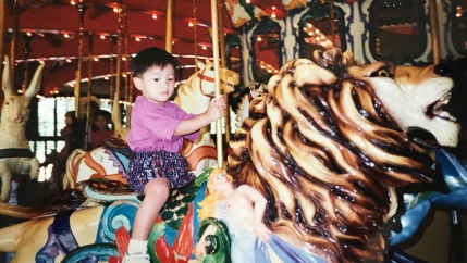 Boy on horse in carousel, looking at camera. Old, scanned photo