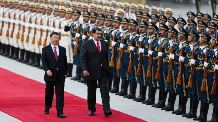 Chinese President Xi Jinping walks next to Venezuela's President Nicolas Maduro in front of a row of Chinese troops