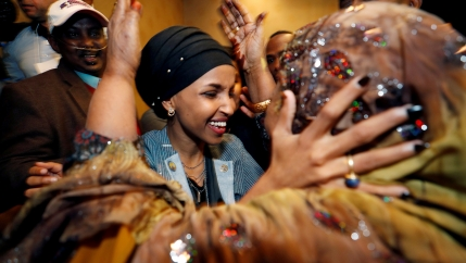 Ilhan Omar clasps her husband's mother's face in her hands as she smiles