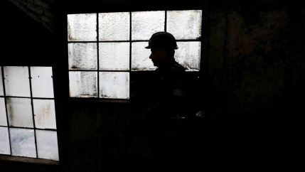 A man wearing a hard hat is silhouetted against old heavy windowpanes in a factory.