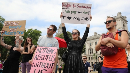 People stand with signs supporting sex worker rights --