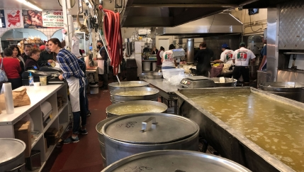 At a counter in a Latino market, customers wait to buy food while workers cook in the back. In the foreground are huge steel pots.