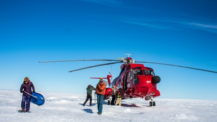 A red helicopter is shown landed on the Greenland ice sheet with team of three professors and three students unload their gear.