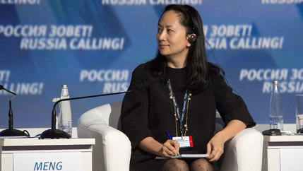 Meng Wanzhou, wearing all black, is shown seated with a pen and notepad at a session of the VTB Capital Investment Forum