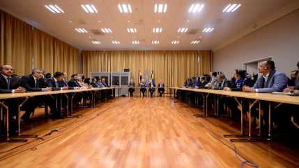 delegates sit across each other in a large room with a wood floor