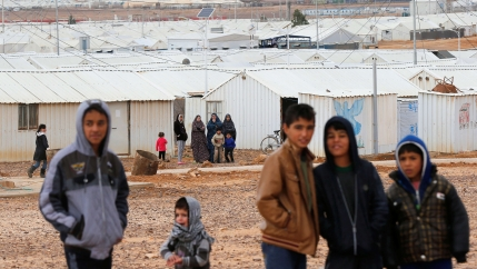 Syrian refugees look at the camera as they stand in front of their homes at Azraq refugee camp