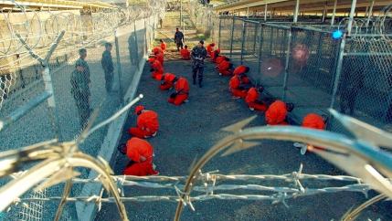 Detainees wearing orange jumpsuits crouch down within a barbed wire protected area.