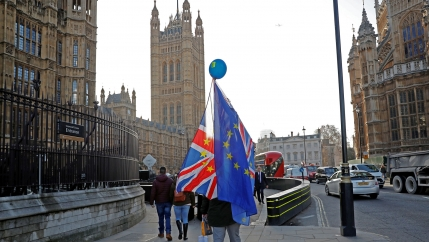 An person is show walking away from the camera carrying both British and EU flags .