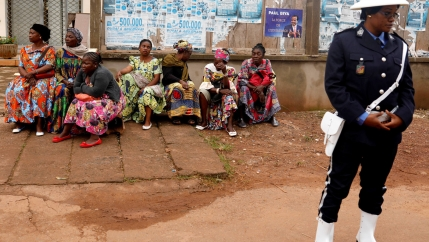 Several women sit outside a polling center against a wall wearing colorful textiles with a policewoman standing guard in front of them.