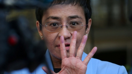 A closeup of Maria Ressa with her hand up in front of her face.