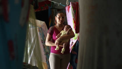 a female prisoner holds her baby in a room with laundry hanging