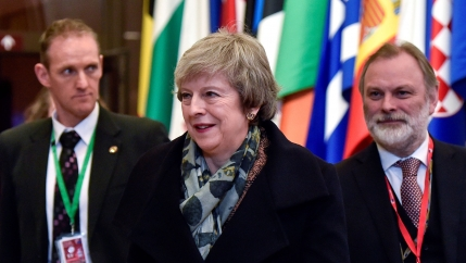 British Prime Minister Theresa May  is shown center wearing a dark jacket and scarf next to Britain's Permanent Representative to the EU Tim Barrow in a suit and red tie.