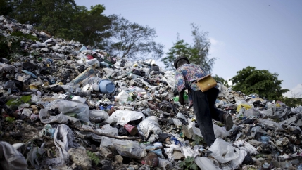 a man climbs a pile of garbage