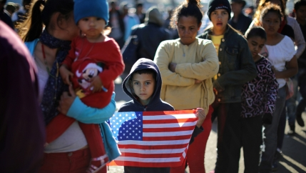 Mother with her son, holding a US flag, waits in line for food.