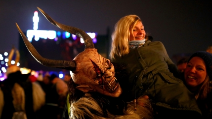 a person wearing a costume of horns, fangs and fur, carries a woman over their shoulder