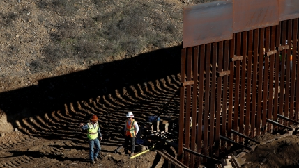 Workers construct border wall.