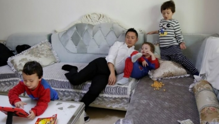 A father rests on the sofa with this three sons in China.