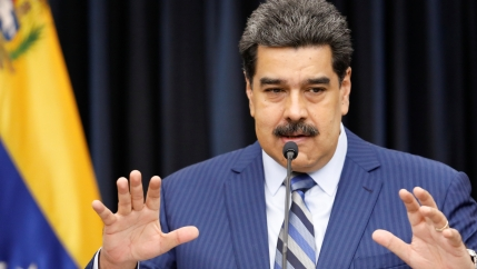 Venezuela President Maduro in blue suit holds his hands out and speaks at news conference.