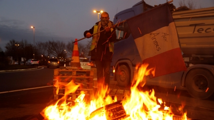 A protester wearing a yellow vest is shown holding a flag near burning debris at the approach to the A2 Paris-Brussels highway, Dec. 4, 2018.