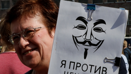 A woman holds a sign in Russian that says