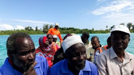 A group of Tanzanians wearing bright colorful clothes ride in a boat.