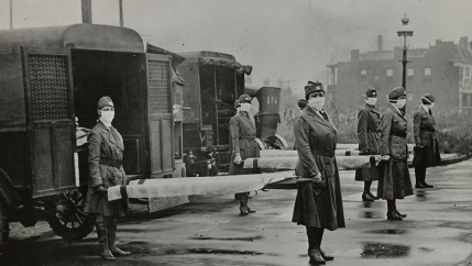 Women in uniform hold stretchers in front of ambulances in this historic photo.