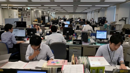 People are working at computers in a large open office