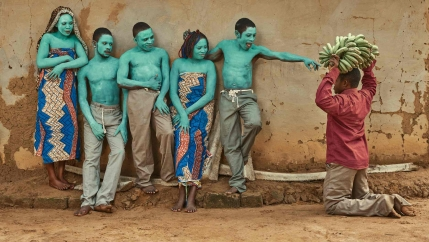 Five people are painted with a light green paint and post together. Another man is on his knees with bananas.