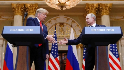 Donald Trump and Vladimir Putin shake hands behind two podiums reading Helsinki 2018