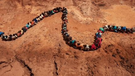 People form a line like a snake on the bed of a dry riverbed