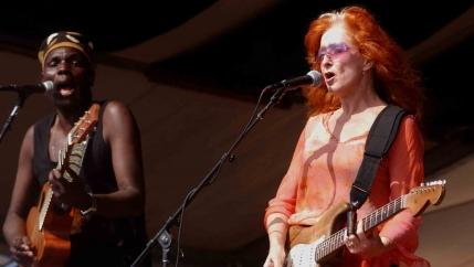 Oliver Mtukudzi, left, plays guitar with Bonnie Raitt.