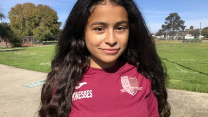 A headshot of Bay Area teen Crista Ramos, who is suing the federal government.She wears a red shirt, has long dark hair, and looks directly into the camera.