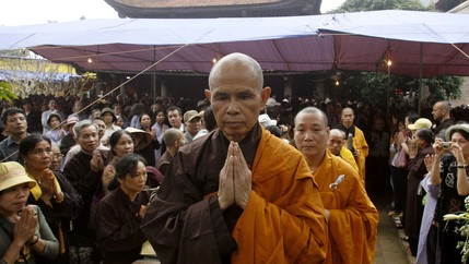 A Buddhist monk walks through a crowd with his hands in a prayer position