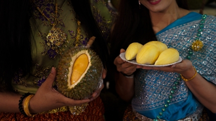 Women dressed in Thai traditional costumes hold durians at a department store in Bangkok