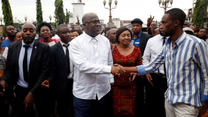 Felix Tshisekedi is shown in a white shirt shaking hands with a suppoert in the streets of Kinshasa, Democratic Republic of Congo.