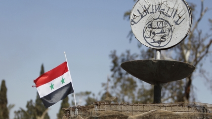 A Syrian national flag flutters next to ISIS slogan