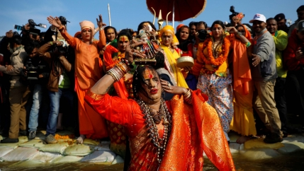 A transgender Indian woman in an orange sari with wet hair in front of a crowd