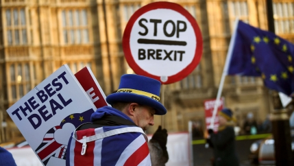 A man with a top hat and UK flag draped around his shoulders holds anti-Brexit protest signs