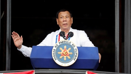Philippine's President Rodrigo Duterte speaks behind a blue podium in a white shirt