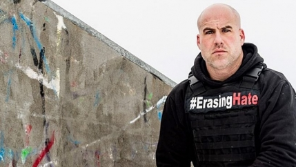 a bald man crouches down next to a graffiti-covered stone. he wears a vest that says