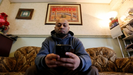A man sits on a couch in his living room.