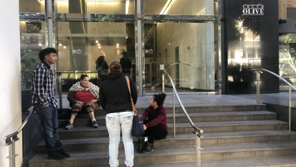 People sit on the steps outside Los Angeles immigration court, which has been closed since Dec. 22 due to a partial government shutdown over funding for a southern border wall.