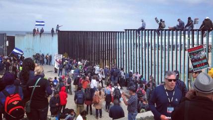 Some people sit on top of a border barrier while a crowd gathers on the ground.