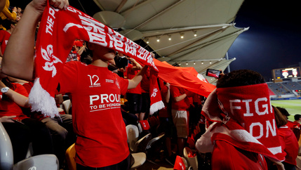 Hong Kong fans cover their faces and boo during the Chinese national anthem, at a friendly soccer match between Hong Kong and Bahrain in Hong Kong, China, November 9, 2017.