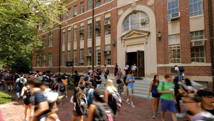 Students walk in front of a tall brick building on a university campus