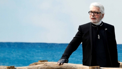 German designer Karl Lagerfeld stands before an ocean backdrop at a fashion show.