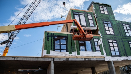 A 65 by 13 foot modular unit is shown with a green insulated side and windows, dangling from a crane.