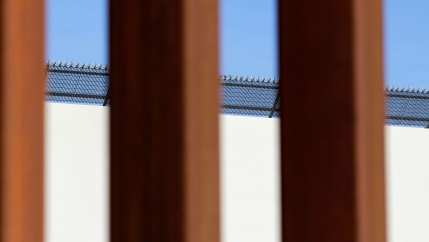 A prototype border wall with large metal spikes on top is seen through the metal slates of the border fence between Mexico and the United States.