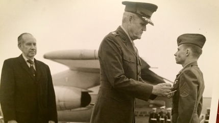 Ken Kraus receives a medal in front of an airplane