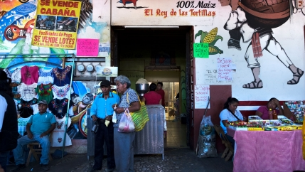 A market is shown in Tlaxiaco, Mexico, with vendors and shoppers.